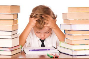 Portrait of a cute little boy sitting in library before books. Isolated over white background.